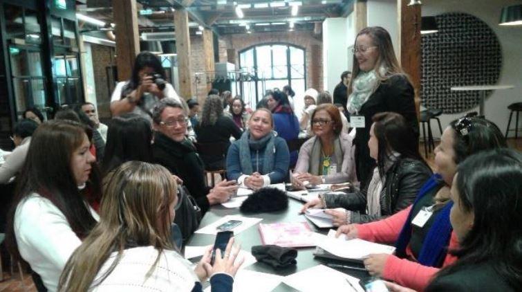 Professoras sentadas ao redor de uma mesa conversam durante workshop