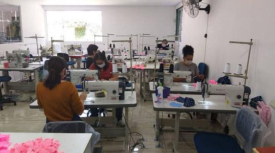Mulheres costuram em máquinas em sala de costura